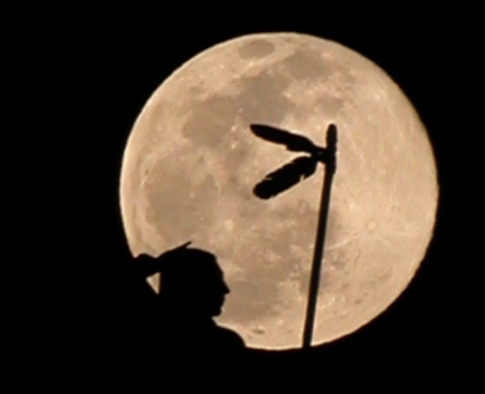 The Guardian statue, which sits atop the dome of the Oklahoma State Capitol, is silhouetted against a full moon over Oklahoma City. Photo by: Ralph Joseph Petroskey